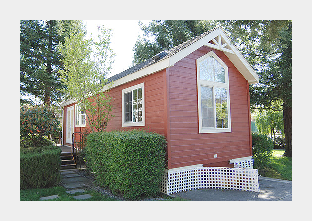 A Tiny House with a Porch and Hedges
